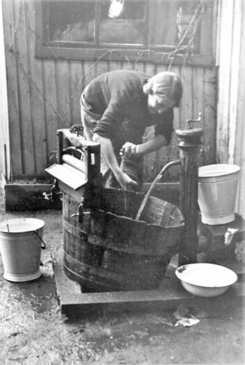 Kvinne vasker tøy utendørs, utstyrt med vannpost. Foto: Nanna Broch