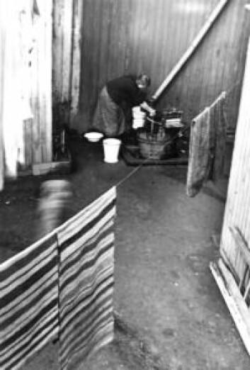 Klesvask, kvinne vasker tøy utendørs, utstyrt med vannpost. Foto: Nanna Broch