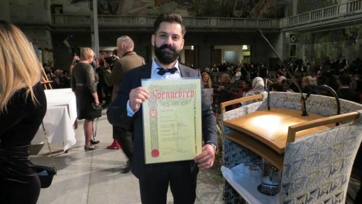 Thaer Abo Issa viser stolt frem svennebrevet som beviser at han er utdannet frisør i Norge. Her fra utdelingen i Rådhuset. Foto: Privat