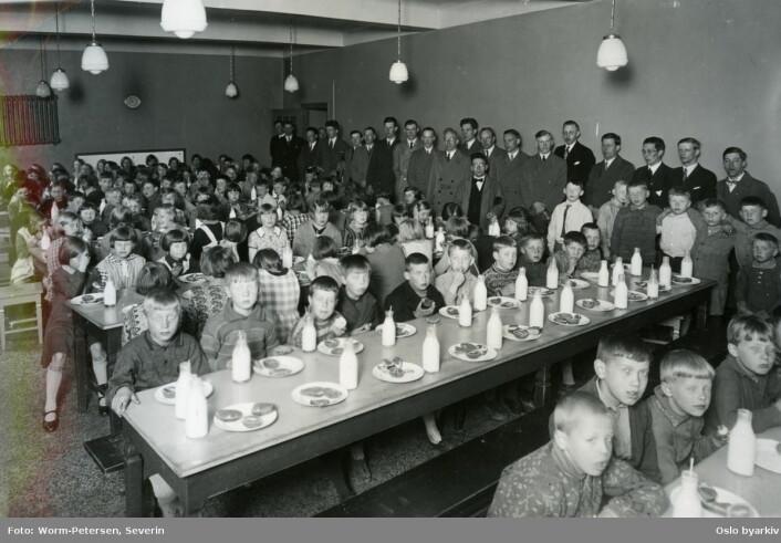 Sagene skole 13. mai 1930, under skolefrokost i matsalen. Elever ved langbord med mat og melkeflasker. Lærere oppstilt langs veggen i bakgrunnen. Forløper til Oslofrokosten. Foto: Severin Worm-Petersen / Oslo byarkiv