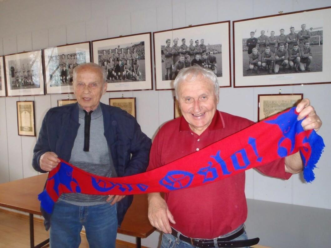 """Veteranene Arne Larsen og Jan Erik """"Puskas"""" Olsen holder skjerfet med påskriften: Ekte Oslo. På veggen henger bilder av Skeids mange mesterlag fra 50-og 60 årene. Foto: Anders Høilund"""