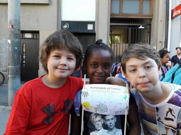 Popstjernene Marcus og Martinus er med på plantingen. Victor til venstre har skrevet på plakaten Maida holder. Maida er fadderbarnet til Linus (t.h) Foto: Anders Høilund