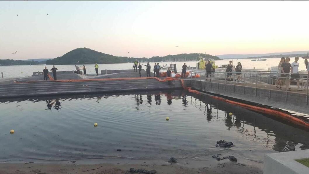 Oljelenser har overtatt etter badegjestene på Sørenga. Brannvesenet har nå lagt ut lenser for å fange opp oljesølet. Foto: Gaute Eiterjord