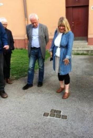 Historiker Gro Røde peker på snublesteinene banket inn i gaten for å minnes historien om jøder som ble deportert og drept i utrydningsleire under 2. verdenskrig. Foto: Kjersti Opstad