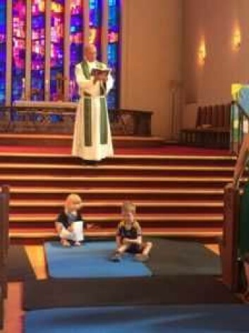 Presten preker i kirka. Barna får lov å leke på gulvet. Foto: Kjersti Opstad