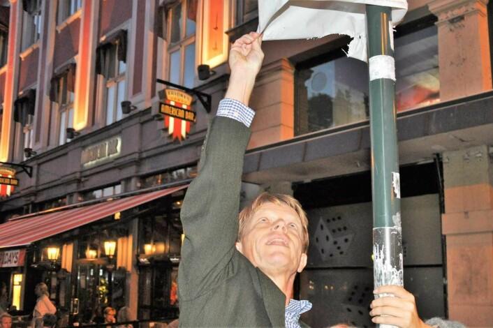 Høyres bystyremedlem Ola Kvisgaard sjekker selv at det er tredd en pose med parkering forbudt-symbolet over skiltet som markerte handikapp-parkering på Karl Johans gate før sommeren. Foto: Arnsten Linstad