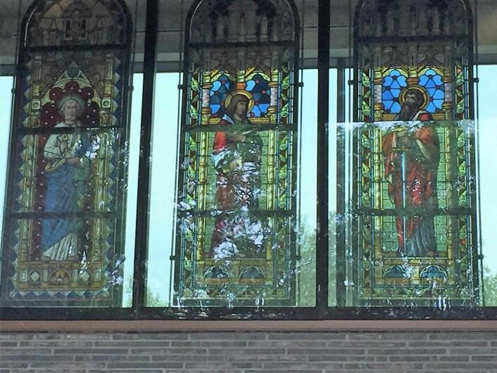 Glassmalerier dominerer den ene veggen i kirken. Foto: Kjersti Opstad