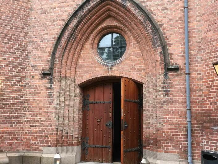 Rød teglstein og tunge tredører viser vei inn i kirken som skal ha 12.500 registrerte sognebarn. Foto: Kjersti Opstad