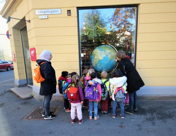 Ungene fra Uranienborg barnehage er bergtatt av Nomadens kjempeglobus. Om noen år sitter ungene selv i butikken og planlegger sine opplevelsesferier. Foto: André Kjernsli