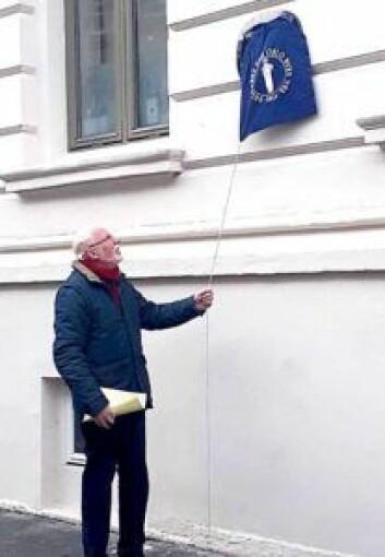 Morten Kolstad trekker i tråden for avdekke det blå skiltet. Foto: Emilie Pascale Bloin Helgheim