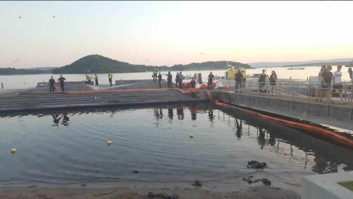 Oljelenser har overtatt etter badegjestene på Sørenga i slutten av mai i år. Brannvesenet la ut lenser for å fange opp oljesølet. Foto: Gaute Eiterjord