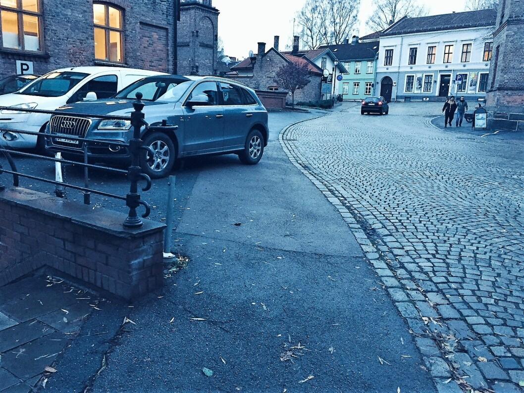 Personbiler har parkert på fortauet ved Beierbrua. På høyre side rett foran de to personene er det malt et privat parkeringsfelt på fortauet (kommer ikke helt frem på bildet). Foto: Einar Spurkeland
