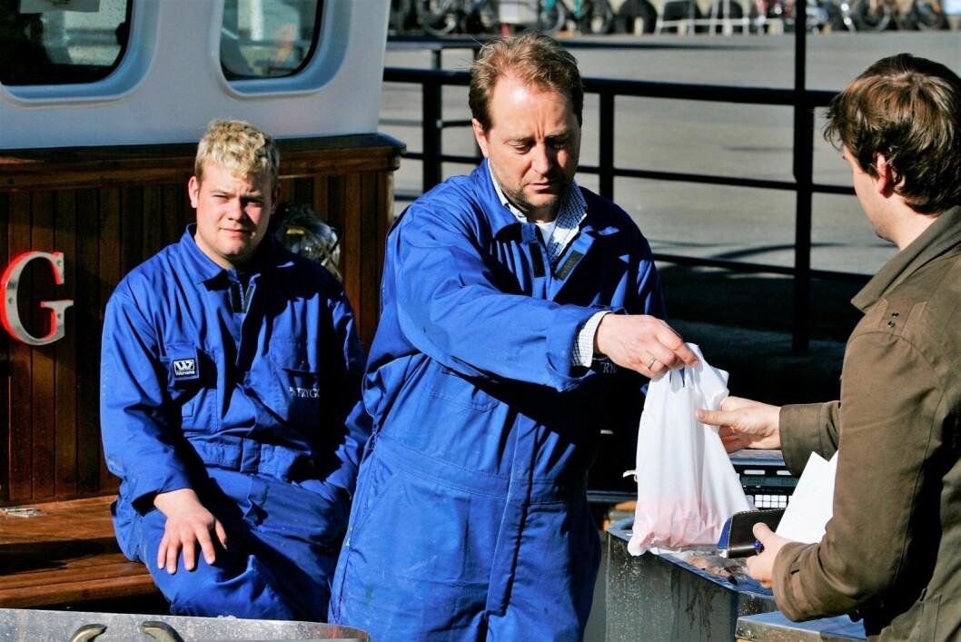"""Kjell Inge Røkke selger selvfiskede reker for 70 kroner literen ombord i """"Trygg"""" på Rådhuskaia i Oslo dagen før 17. mai i 2007. I bakgrunnen Thomas Hammerø.  Foto: Erlend Aas / SCANPIX"""