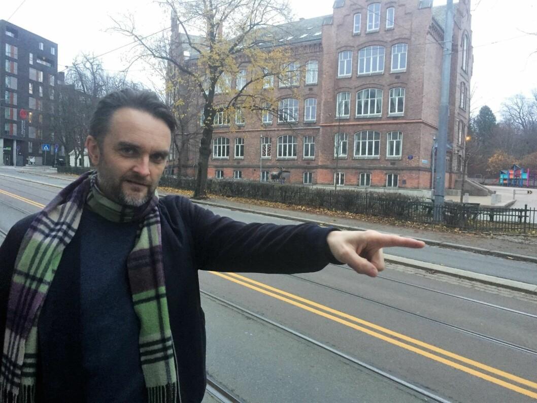 Pappa Stian Schjelderup peker ut skoleveien for barna til Laggegata skole, i bakgrunnen. Foto: Vegard Velle