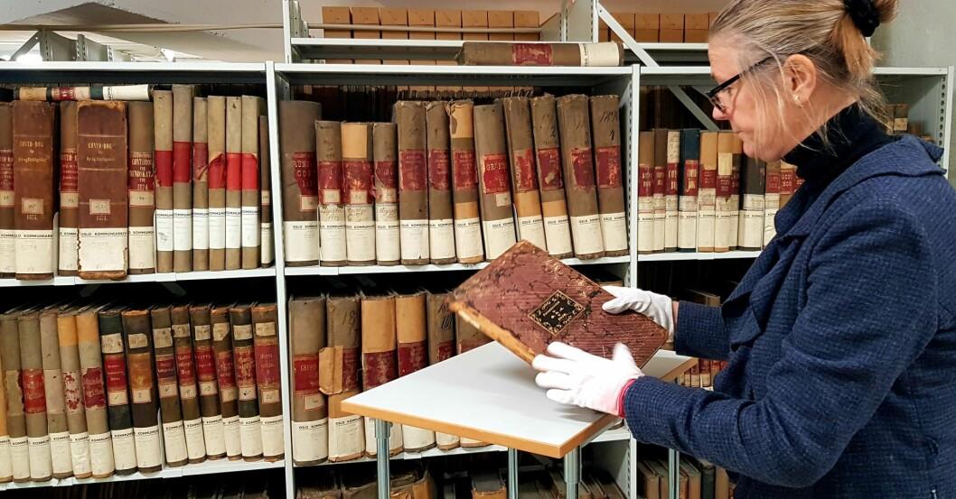 Kirsti Gulowsen, spesialkonsulent, Oslo byarkiv, viser frem en pasientprotokoll fra 1850 (Oslo Hospital). Foto: Kulturetaten