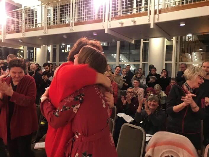Oslo SVs toppkandidater ved valget neste høst, Marianne Borgen og Sunniva Holmås Eidsvold, gir hverandre en klem mens fylkespartiets medlemmer gir stående applaus. Foto: Jens Aas-Hansen / Oslo SV