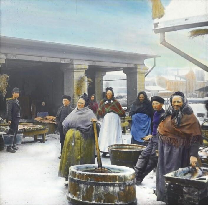 Fiskekoner ved Sadelmakerbrygga. Håndkolorert fotografi av Anders B. Wilse / Oslo museum