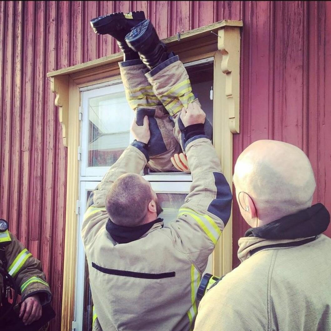 Ingen skal si at Oslos brannfolk ikke er kreative når de hjelper byens innbyggere. Slik tok brannfolkene seg inn i det tomme trehuset på Kampen da røykvarsleren slo ut. Foto: Oslo brann- og redningsetat