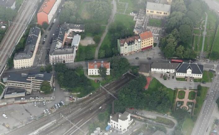 Slik var tomten, til venstre for det hvite huset midt i bildet, før trærne ble felt. Oslo Ladegård til høyre i bildet. Utsnitt av oversiktsfoto fraReiulf Ramstad arkitekter