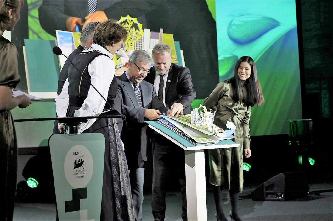 Her blir Oslo offisielt erklært som ny miljøhovedstad i Europa. Miljøbyråd Lan Marie Berg ser spent på mens Raymond Johansen og EU-kommisjonær Karmenu Vella blar over til Oslo-kapittelet i EUs miljøprotokoll. Foto: André Kjernsli