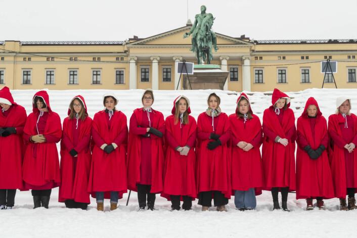 Komiker og samfunnsdebattant Sigrid Bonde Tusvik protesterte mot regjeringen sammen med 30 andre kvinner i «Handmaids Tale»-utkledning. The Handmaid's Tale er en dramaserie om et dystopisk samfunn etter en ny amerikansk borgerkrig der kvinner blir tvunget til å være konkubiner. Foto: Heiko Junge / NTB scanpix