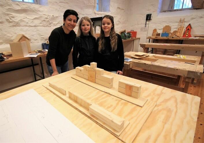 Femteklassingene Vera og Alba (t.v) har sammen med sløydlærer Andrea vært med på å lage en tremodell av den nye skolegården. Foto: André Kjernsli
