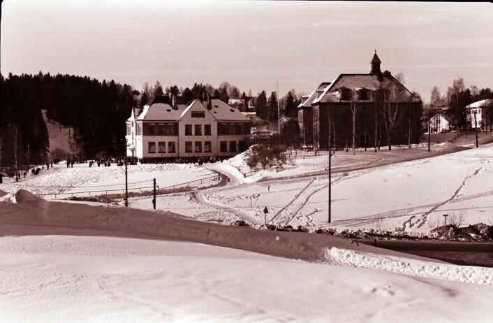 Østensjø skole med Rognerudbakken i lia i bakgrunnen i 1967. Helt til opp på 1970-tallet arrangerte skolen hopprenn i skoletiden. Fortsatt kan man se rester av Rognerudbakken i skogen på andre siden av Østensjøveien. Foto: Østensjø historielag.