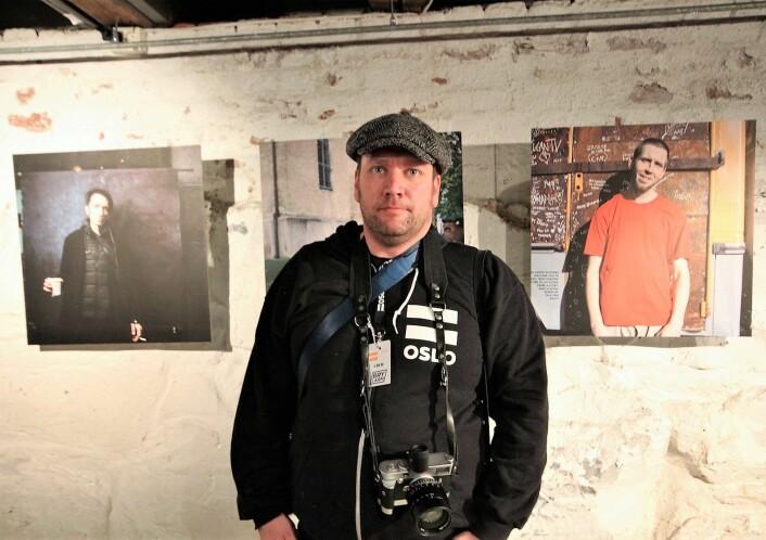 Niklas Mørkland foran noen av portrettene han har tatt av =Oslo-selgerne. Foto: André Kjernsli