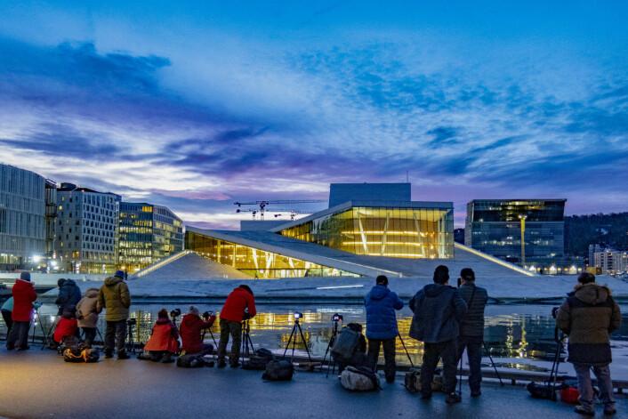 Turister tar bilder av Operaen i Bjørvika en tidlig morgen. Med sine 19.000 kvadratmeter marmorflate og karakteristiske arkitektur har operahuset etter åpningen i april 2008 blitt en av hovedstadens store turistattraksjoner. I bakgrunnen reiser Lambda og det nye Munch-museet seg. Foto: Paul Kleiven / NTB scanpix