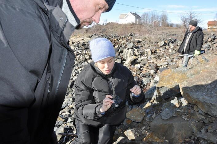 Eirik fra Jobben viser miljøbyråd Lan Marie Nguyen Berg all den gamle, porøse og farlige plasten som er skylt inn under steinfyllingen ved båtopplagsplassen på Gressholmen. Foto: Arnsten Linstad