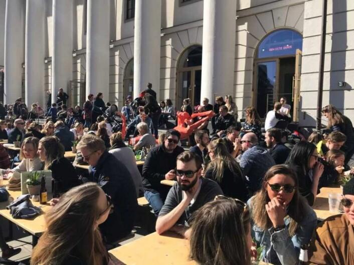 Fullt av folk som tar årets første utepils foran Mathallen i Torggata. Foto: Christen Wikborg