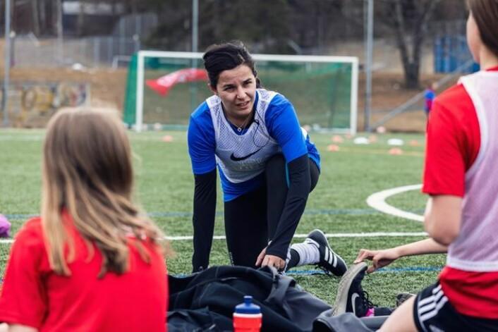 Ap-politiker og tidligere fotballspiller Zaineb Al-Samarai stilte opp som trener for jentene på fotballskolen hos Haugerud IL. Foto: Tine