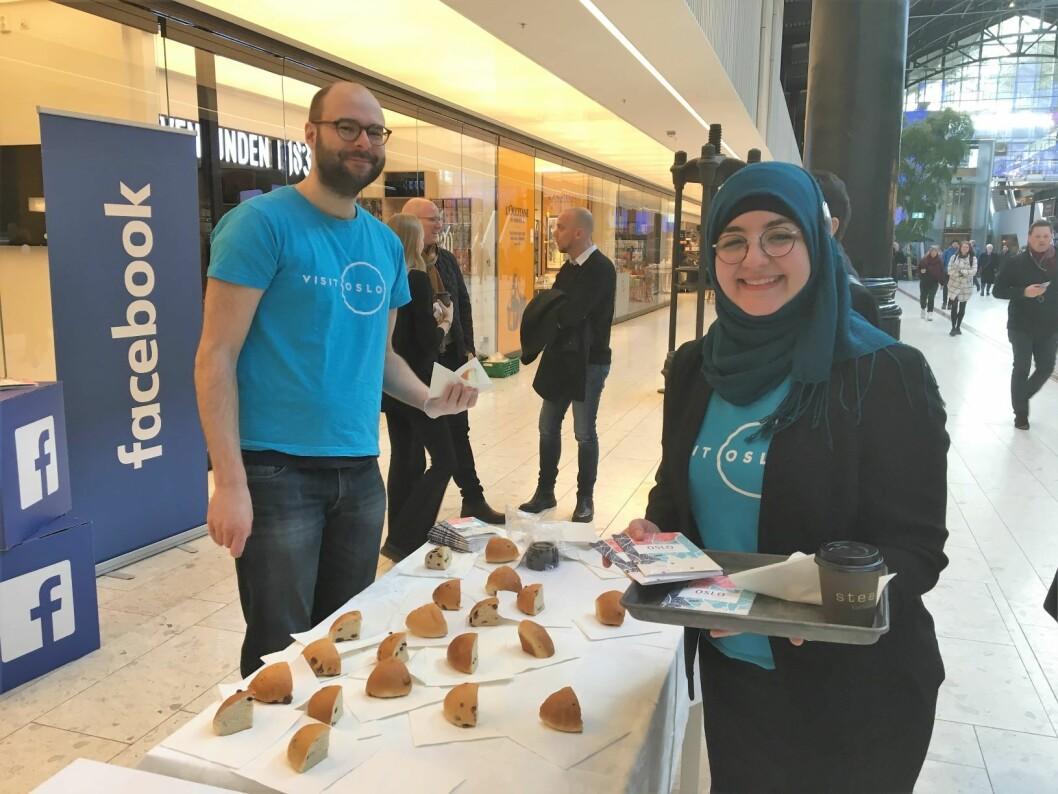 Bernhard Probst og Sakina Benmalek serverer boller, kaffe og byguide til menneskene som går gjennom Østbanehallen på Oslo S. Foto: Vegard Velle