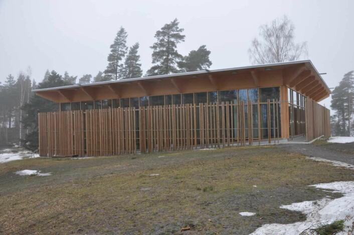 Hegnhuset er bygget rundt Kafèbygget der 13 AUF`ere ble skutt og drept. Hver av trestolpene symboliserer overlevende som hegner om de drepte. Foto: Arnsten Linstad