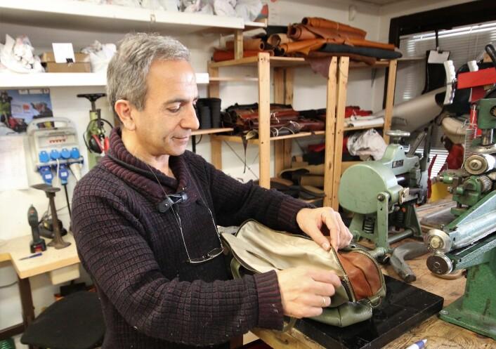 Gholam H. Nasiri har akkurat reparert ei skinnveske for en kunde. Foto: André Kjernsli