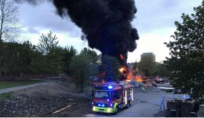 Tilsammen sju biler fra brann- og redningsetaten jobbet lørdag kveld med å slukke brannen i bygningsmaterialer ved Jordal Amfi. Foto: Stian Solberg
