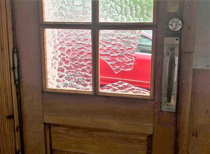 Da politiet kom viste det seg at vindusruta i inngangsdøren til oppgangen i bygården var knust. Og det var blodspor på veggene i oppgangen. Foto: Jorunn Mathisen