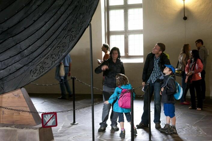Turister ser på Osebergskipet. Det har vekket internasjonal oppsikt at norske myndigheter ikke setter av penger til vern av vikingskipene på Bygdøy. Foto: Tor Erik Schrøder / NTB scanpix