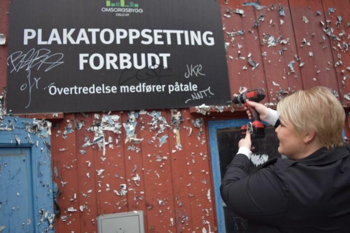 Byråd Marte Scharning Lund skrur ned skiltet med plakatforbud. Når det blir liv inne, blir det slutt på forsøplingen utenfor. Foto: Magnus Evenstuen