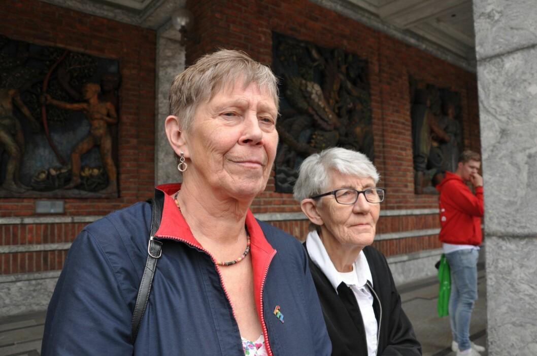 Solvår Foss (til v.) og Brit Lie ser regnbueflagget heises ved Oslo rådhus. Paret bor sammen ved Kirkens bymisjons omsorgsboliger for eldre på Kampen. Foto: Arnsten Linstad