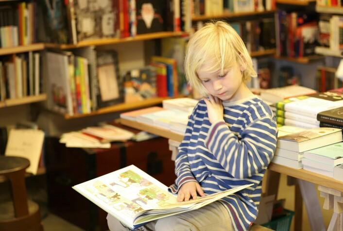 Lars Mørland (7) fordyper seg i tegneserier mens pappa titter i bokhyllene. Foto: André Kjernsli
