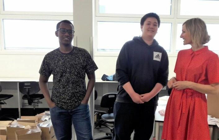 Hamza Omar og Patrick Guldbrandsen (i midten) forklarer skolebyråden arbeidsoppgavene de har for å sette i stand Ipads til elevene til skolestart. Foto: Anders Høilund
