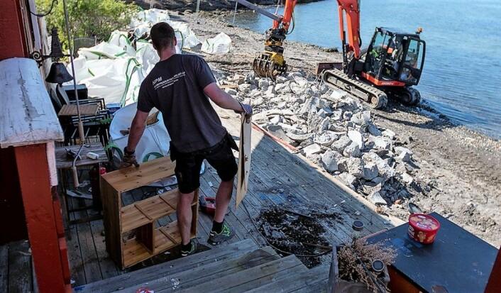 Her bærer byggeleder Knut-Marius Olafsen Sjåstad ut inventar fra hytta før rivingen begynner. Foto: Thor Christofer Brøgger Langfeldt