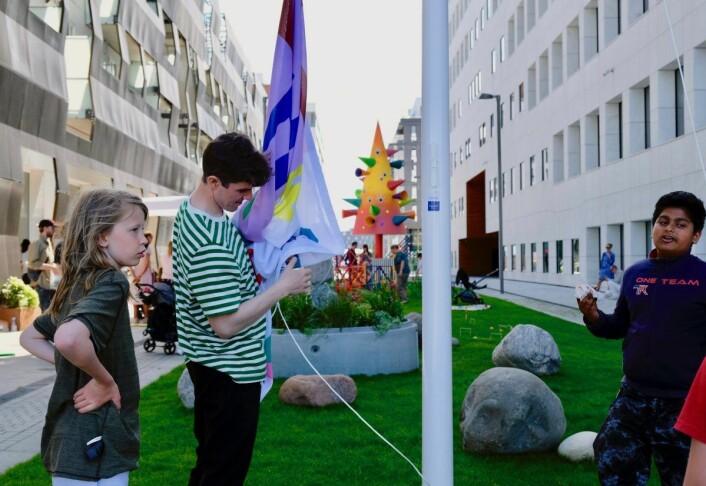 Barna ved Tøyen Biblio heiser et av flaggene som skal vaie i vinden over den nye parken. Foto: Emilie Pascale