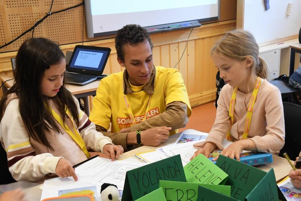 Sommerskoleassistent Leon Mjaaland (19)følger medmens elevene Yolanda (t.v) og Helene tegnermonstre. Foto: Christian Boger