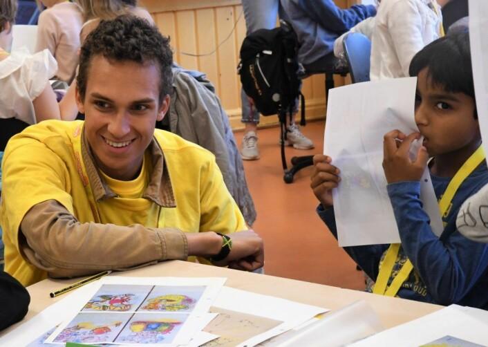 Sommerskoleleev Mohammed Ayman tar en bit tegningen, mens assistent Leon Mjaaland hjelpr en medelev. Foto: Christian Boger