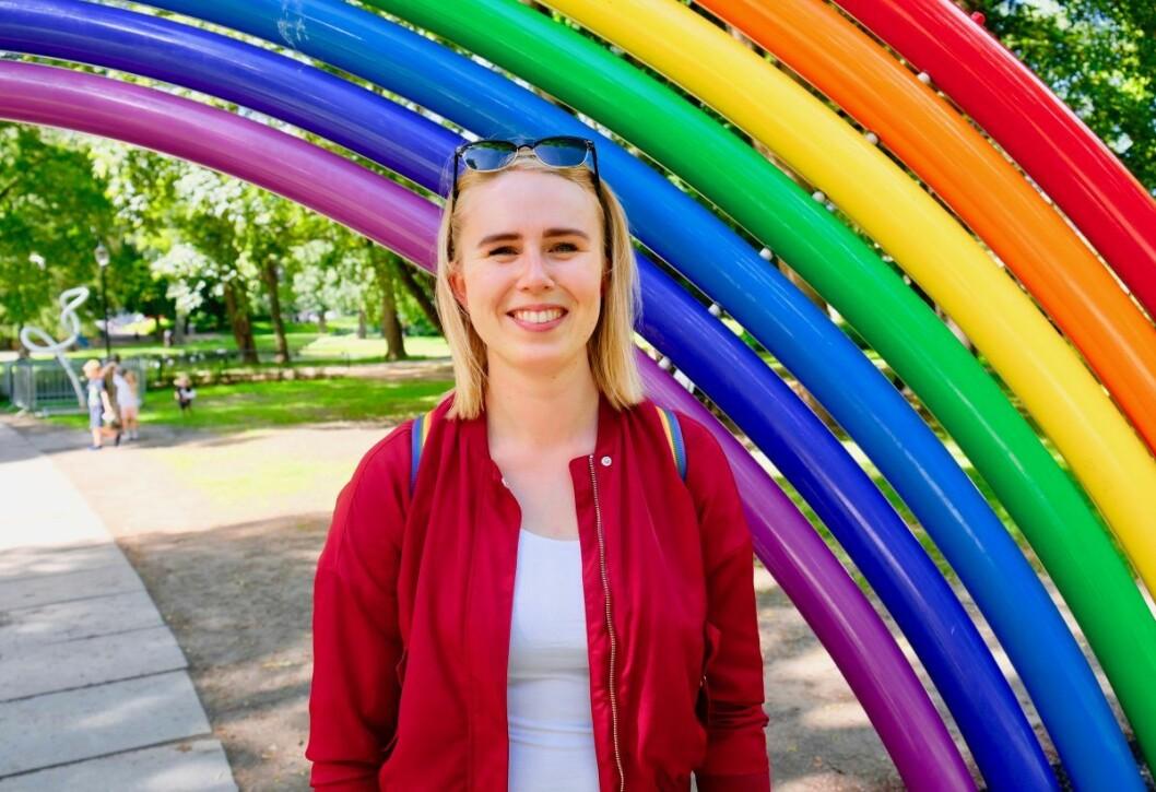 En smilende Fanny Sandberg Vik under regnbuefiguren i Slottsparken. Foto: Emilie Pascale