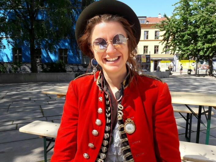 Elona Planman nyter sola, og en nystekt vaffel på Schous plass på Grünerløkka. Den røde jakka er hennes varemerke, og følgesvenn. Foto: Anders Høilund