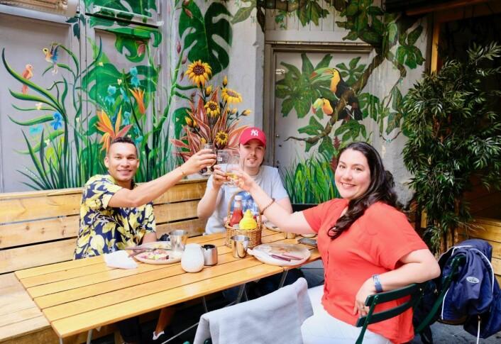 Café Sara har en innvendig bakgård med pent dekorerte vegger, noe disse tre vennene gladelig skåler over. Foto: Emilie Pascale