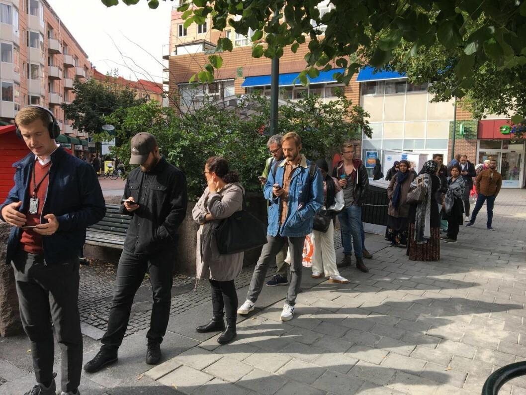 Folk smurte seg med tålmodighet i køen foran stemmelokalet. Takk de høyere makter for smarttelefonen. Foto: Vegard Velle